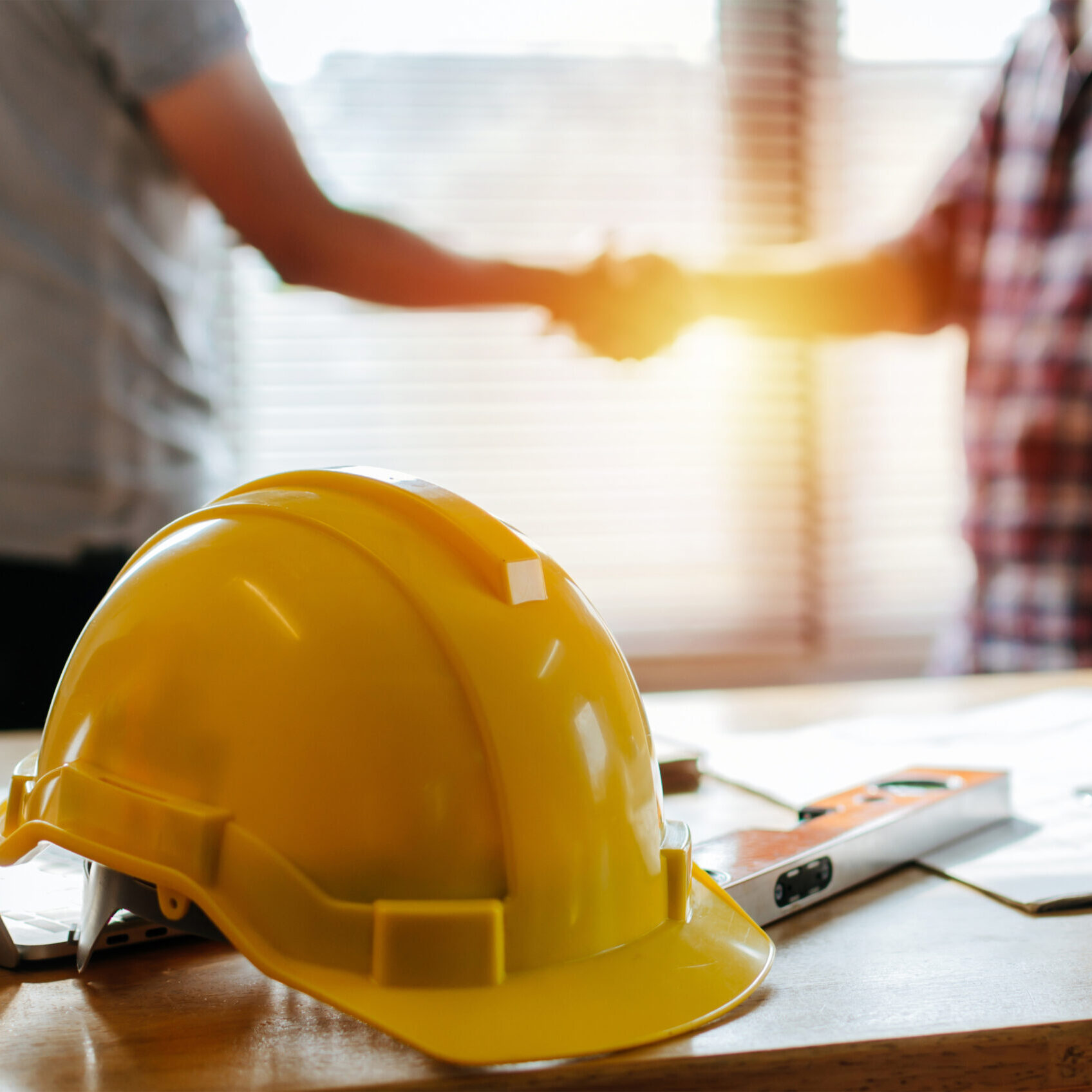 hard hat with men shaking hands in the background